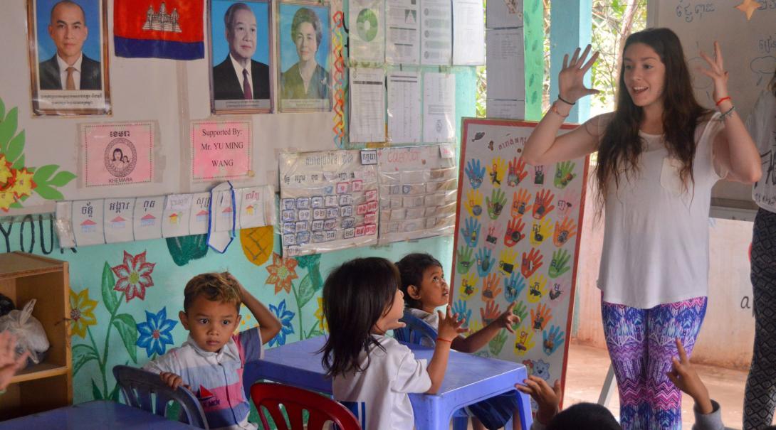 En volontär leker lärande lekar med förskolebarn under hennes volontärresa utomlands.